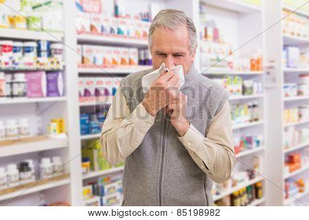 Sick customer sneezing on tissue in the pharmacy