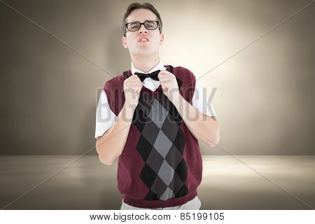 Geeky hipster fixing his bow tie against red background with vignette