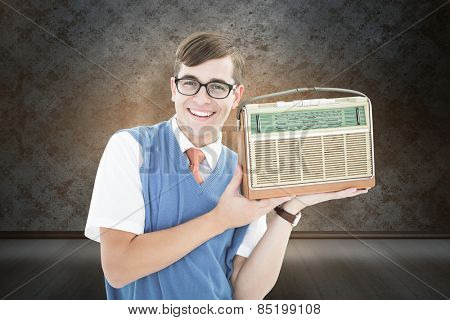 Geeky hipster listening to retro radio against orange background with vignette
