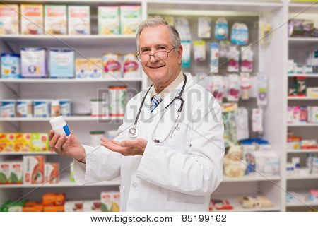 Smiling senior doctor showing medication in the pharmacy