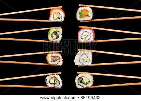 Set of sushi pieces in chopsticks, isolated on black background