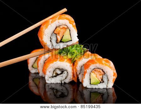 Delicious sushi rolls served on black table with chopsticks
