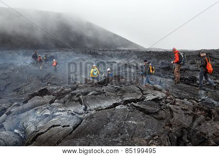 Tourists Hiking On Hot And Steaming Lava Field Eruption Tolbachik Volcano On Kamchatka. Russia