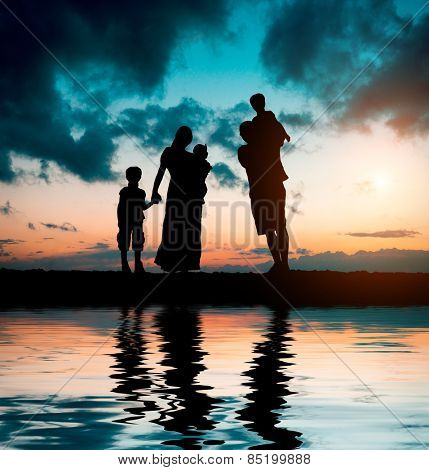 happy big family on a background of the magnificent sunset over the sea