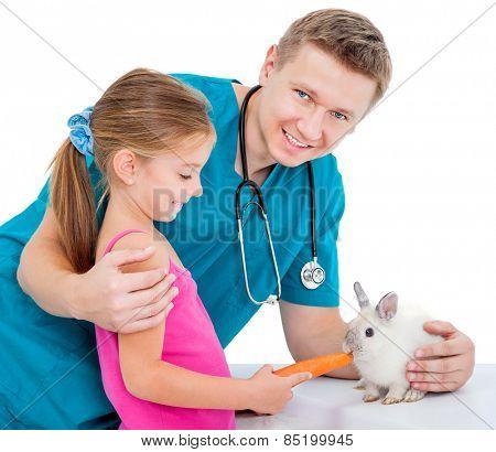 veterenarii and a pretty  little girl feeding rabbit carrot