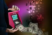 stock photo of automatic teller machine  - man hand showing teller machine in color background - JPG