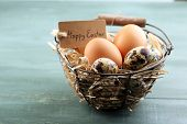 foto of bird egg  - Bird eggs in wicker basket with decorative flowers on color wooden background - JPG