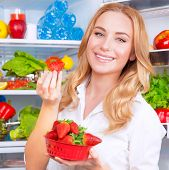 stock photo of strawberry blonde  - Closeup portrait of beautiful female eating strawberry - JPG
