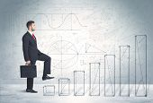 stock photo of climb up  - Business man climbing up on hand drawn graphs concept on background - JPG