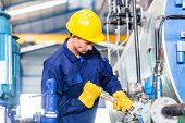 picture of construction machine  - Technician in Asian factory at machine maintenance working with wrench - JPG