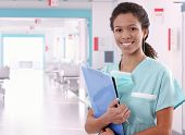 picture of ward  - Young happy afro american nurse standing at hospital ward with clipboard and pen in hand - JPG