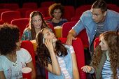 stock photo of annoyance  - Annoying woman on the phone during movie at the cinema - JPG