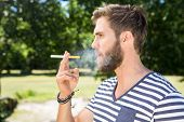 pic of electronic cigarette  - Hipster smoking electronic cigarette on a summers day - JPG