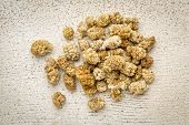 picture of mulberry  - a pile of dried white mulberry fruit against rustic barn wood - JPG