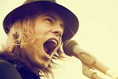 foto of shout  - Young man with long hair and hat singing - JPG