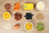picture of containers  - Various food products containing vitamins on wooden background - JPG