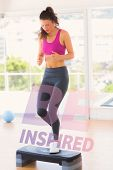 picture of step aerobics  - Full length of a fit woman performing step aerobics exercise against be inspired - JPG