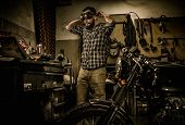 picture of rockabilly  - Mechanic preparing ford lathe works in motorcycle customs garage  - JPG