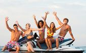 foto of jet  - Group of happy multi ethnic friends sitting on a jet ski - JPG