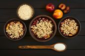 pic of crisps  - Overhead shot of three rustic bowls filled with baked plum and nectarine crumble or crisp photographed on dark wood with natural light - JPG