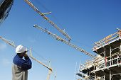 picture of engineering construction  - building worker directing large construction cranes - JPG