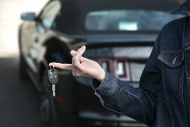 picture of muscle-car  - Woman holding keys to new car in driveway - JPG