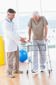 stock photo of zimmer frame  - Senior man on zimmer frame with therapist in fitness studio - JPG