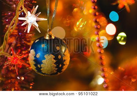 Blue Bauble In Christmas Tree Surrounded By Colourful Lights