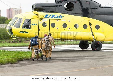 Rescuers load into helicopter MI-8