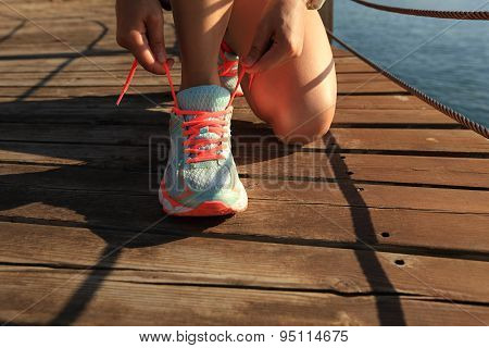 young fitness woman runner tying shoelace on sunrise seaside trail