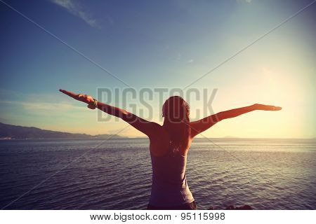 young cheering woman jogger open arms at sunrise seaside,vintage effect
