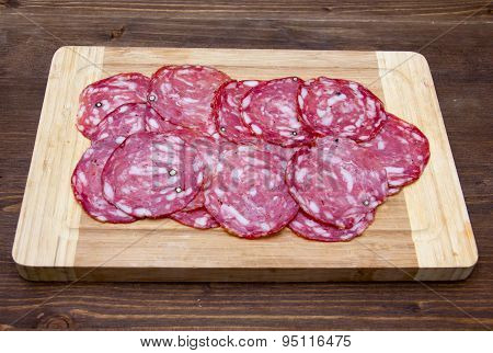 Slices of salami on cutting board on wood