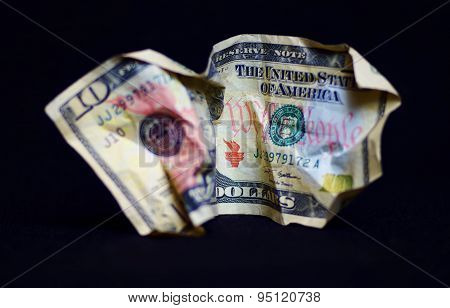 A crumpled US Ten Dollar Bill over a black background