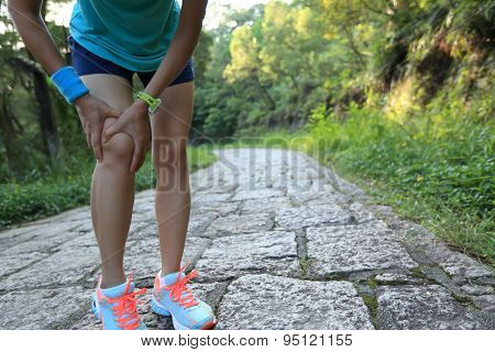 young woman runner hold her sports injured knee