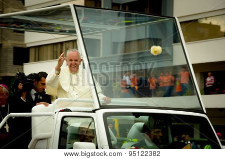 Clear shot of Pope Francis standing on popemobile and waving in camera direction as motorcade drives