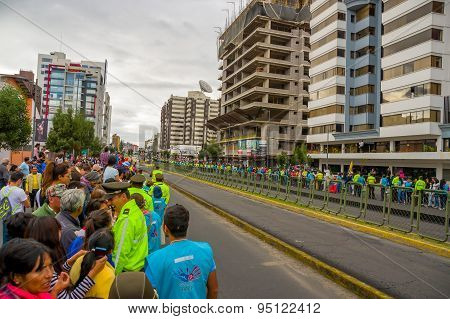 Crowds of people in Quito city street waiting for Pope Francis motorcade to arrive as numerous polic