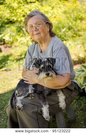 Senior 70S Woman Holding Her Black And Silver Mini Schnauzer Dog Sitting Outdoor