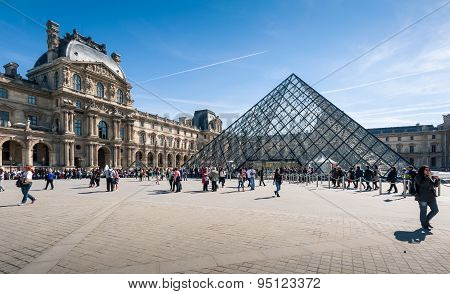 Tourists in the Louvre's central courtyards with the Louvre pyramid and palace