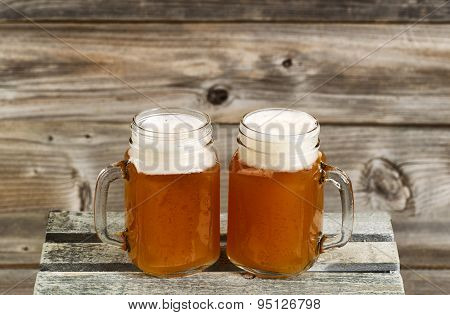 Two Pints Of Fresh Cold Beer On Top Of Wooden Crate With Rustic Wood In Background