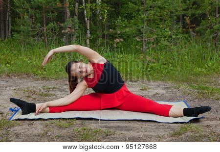 Pretty Woman Doing Yoga Exercises In The Woods