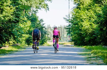 Young pair of professional cyclists riding on the road