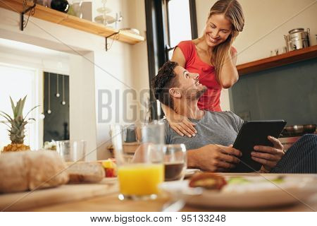 Happy Young Couple In Their Kitchen In Morning