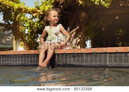 Cute Girl Sitting On The Edge Of A Pool Looking Away