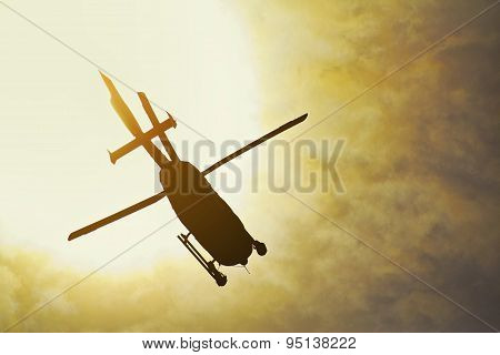 Silhouette Of A Helicopter Flying In The Rays Of The Setting Sun