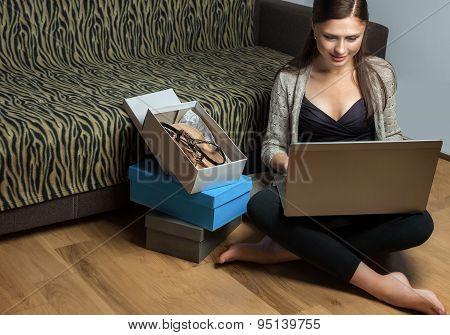 woman doing online shopping from laptop site at the flor