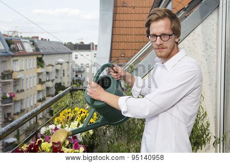 Young Man Watering Plants On Balcony