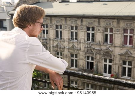 Young Man Looking At An Old Apartment Building