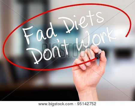 Man Hand writing Fad Diets Don't Work with black marker on visual screen.