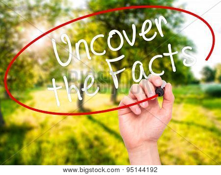 Man Hand writing Uncover the Facts with black marker on visual screen.