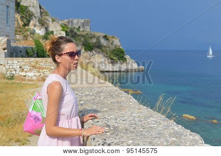 Girl Looking At The Sea From The Fortress Wall Wearing Pink Dress And Sunglasses